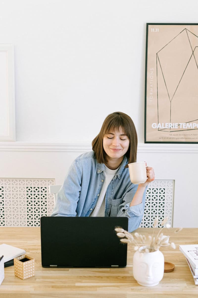Woman smiles as she looks at her computer for a virtual work party