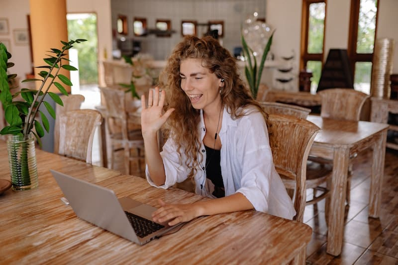 A woman waves to coworkers on a virtual happy hour